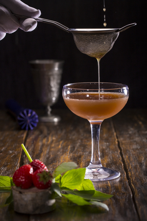 Strawberry and mint cocktail, on a dark wooden background, filtered through a sieve Stock Photo