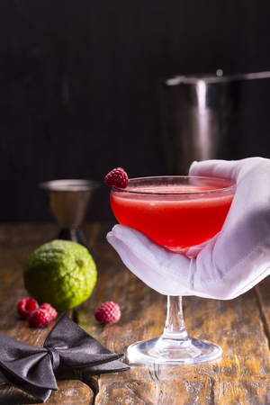 Raspberry cocktail with berry and accessories on a dark wooden background