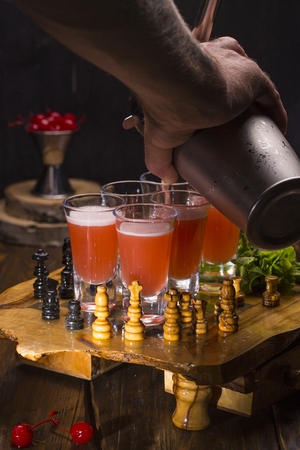 An alcoholic cherry shot-set with mint on a chessboard