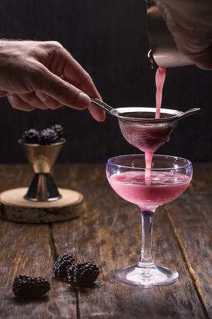 The blackberry cocktail with berries on a dark wooden background filtered through a sieve