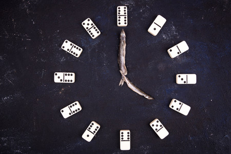 Stunden von Dominosteinen und Pfeilen von Fischen auf einem dunklen konkreten Hintergrund. Vier Stunden Standard-Bild - 75724986