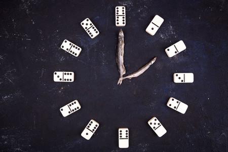 Stunden von den Dominosteinen auf einem dunklen konkreten Hintergrund. Zwei Stunden Standard-Bild - 75724988