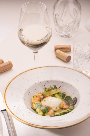 jams: Asparagus with sauce, mussels, goose egg in a white round plate, on the table served by a white cloth with devices