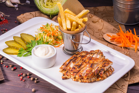 Slices of the marinated fried meat with salad and pickles
