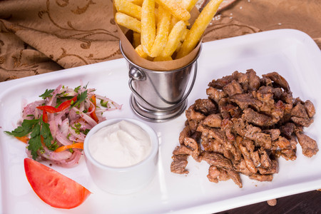 Pieces of braised beef with onions salad and sour cream sauce, is served with French fries Stock Photo