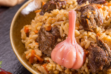 stewing: A lamb with stewed rice, with garlic and spices, with carrots and vegetables