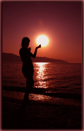 Silhouette of a girl who touches the sun photo