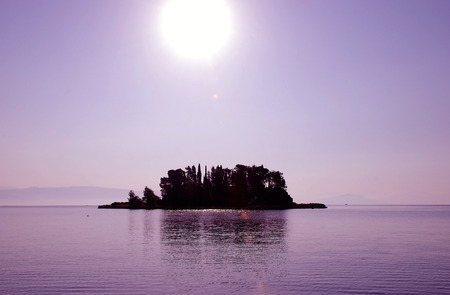 dinghies: Sunset on a Mouse Island on the Island of Corfu in Greece Stock Photo