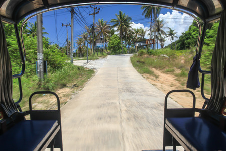 Traveling on the adventure ride Tuk Tuk in southern island of Thailand.