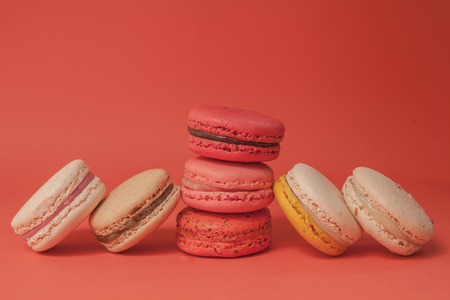 stacked up: Pile of colorful macaroons stacked up like a tower and macarons on their two sides in red pastel isolated background