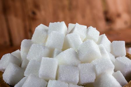 Stapel der Zuckerwürfel über Holzuntergrund