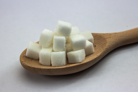 imply: Sugar Cubes on Spoon on Isolated White Background with Harsh Shadow, which can be used to imply dark side of Sugar Stock Photo