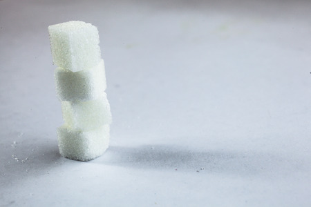 imply: Pile of Sugar Cubes Stacking on Isolated White Background with Harsh Shadow, which can be used to imply dark side of Sugar