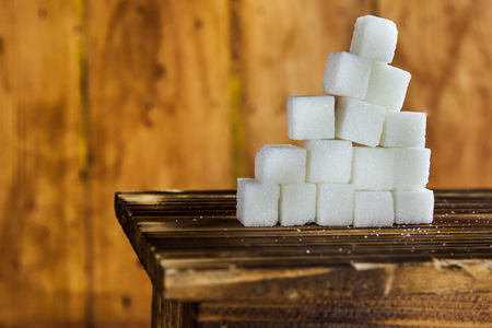 white sugar: Pile of Sugar Cubes Stacking on Table over Wooden Background Stock Photo