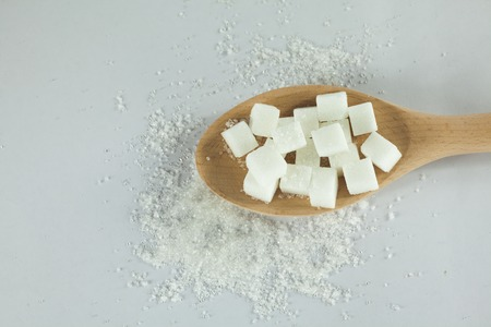high calorie: Sugar Cubes on Spoon with granulated sugar on Isolated White Background Stock Photo