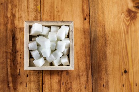 unrefined: Aerial View of Sugar Cubes in Square Shaped Bowl with Unrefined Sugar spill over in Wooden Background