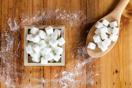 Aerial View of Sugar Cubes in Square Shaped Bowl and Spoon with Unrefined Sugar spill over in Wooden Background Stock Photo