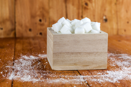 unrefined: Sugar Cubes in Square Shaped Bowl with Unrefined Sugar spill over in Wooden Background