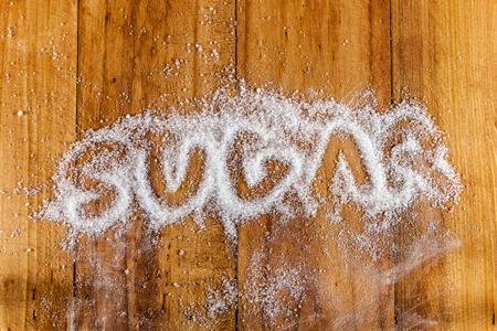 azucar: La palabra escrita de az�car en un mont�n de az�car blanco granulado con cuchara de terrones de az�car sobre fondo de madera