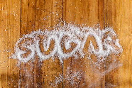 sugar cubes: The word sugar written into a pile of white granulated sugar with spoon of sugar cubes over wooden background