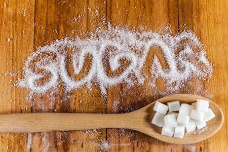 The word sugar written into a pile of white granulated sugar with spoon of sugar cubes over wooden background