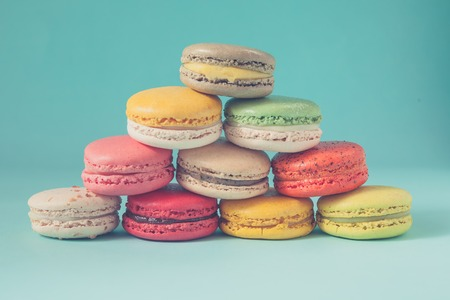 stacked up: Pile of colorful macaroons stacked up like a tower in blue turquoise pastel isolated background - in vintage tone