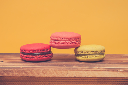 stacked up: Pile of colorful macarons stacked up in yellow pastel isolated background on wood table