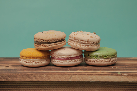 stacked up: Pile of colorful macarons stacked up like a tower in blue turquoise pastel isolated background on wood table Stock Photo