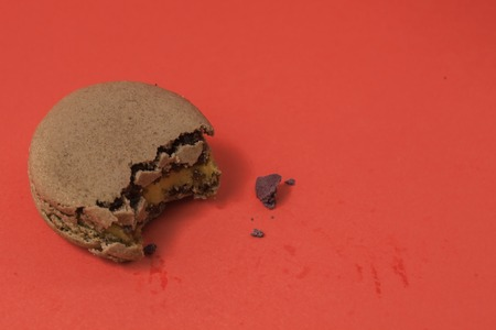 cookies: Dark green color of bitten macaron on the wood table in red pastel isolated background - top view perspective Stock Photo