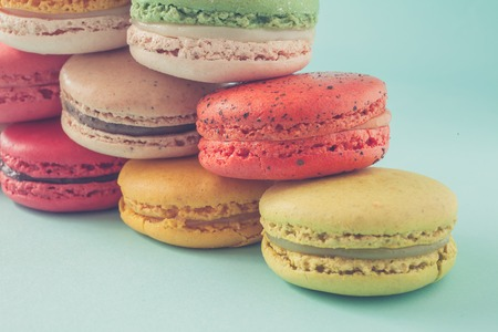 stacked up: Pile of colorful macaroons stacked up like a tower in turquose pastel isolated background (Selective focus) - Closeup Stock Photo