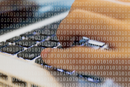 Double exposure of a programmer coding on his laptop dissolved with binary code background Banque d'images