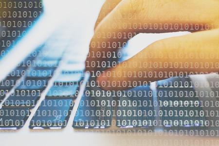 Doppelbelichtung eines Programmierers Codierung auf seinem Laptop mit Hintergrund des binären Codes gelöst Lizenzfreie Bilder