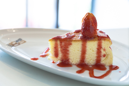 favorite colour: Strawberry Cheesecake decorated with red sweet sauce in the white background. Stock Photo