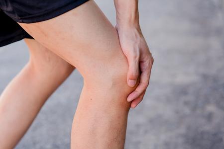 sprained joint: Runner touching painful knee. Athlete runner training accident. Sport running knee sprain. Stock Photo