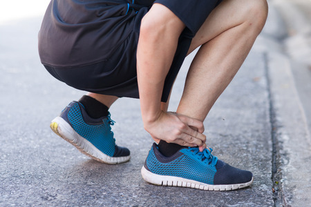 Runner touching painful twisted or broken ankle. Athlete runner training accident. Sport running ankle sprain. Stock Photo