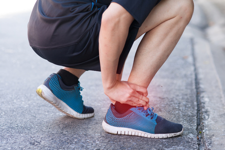 sprained joint: Runner touching painful twisted or broken ankle. Athlete runner training accident. Sport running ankle sprain. Stock Photo