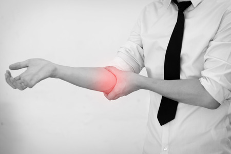 elbow pain: Office Man touching painful elbow. Pain in a man elbow. Stock Photo