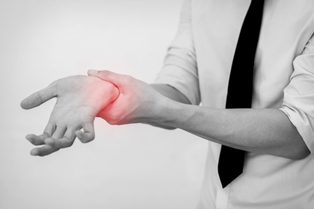 Office Man touching painful wrist. Pain in a man wrist. 스톡 콘텐츠