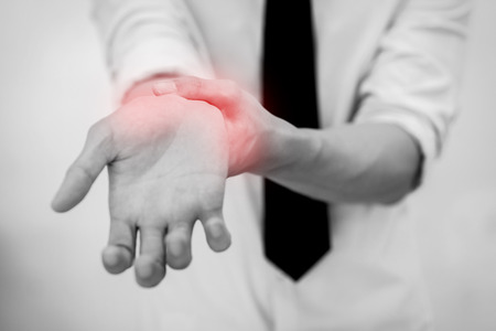 wrist pain: Office Man touching painful wrist. Pain in a man wrist. Stock Photo