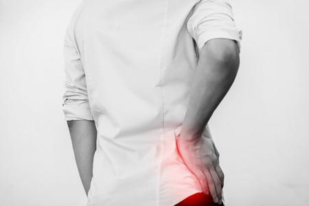 腰の痛みを持つカジュアルなオフィス シャツの若い男 写真素材