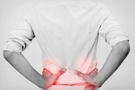 dolor de espalda: Hombre joven en el dolor de la cadera ocasional camisa de la oficina que tiene Foto de archivo