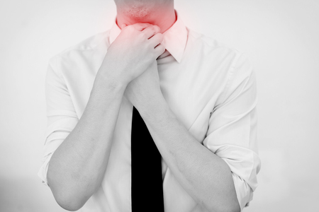 Man Having painful Sore Throat. Touching neck. Isolated white background Imagens