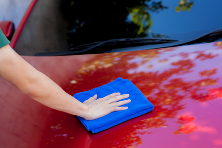 lavar: lavado de hombre joven y limpia un coche en el exterior