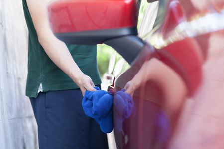 car polish: Young man washing and wiping a car in the outdoor