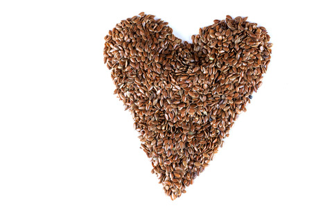 brown flax: a pile of brown flax seeds in heart shape form on isolated white background Stock Photo