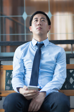 Asian exhausted businessman sitting in corporate building Stock Photo