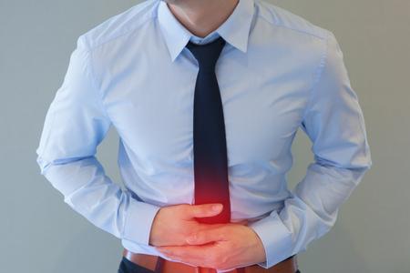 Hombre en Ministerio del uniforme que tiene un dolor de estómago / intoxicación alimentaria / problemas estomacales