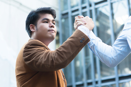 grasping: Asian businessman grasping hands with his trusted colleague
