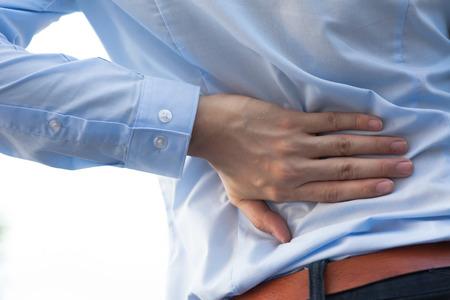 personas de espalda: Hombre en uniforme de oficina que tiene la espalda tema del dolor  lesiones en la espalda Foto de archivo