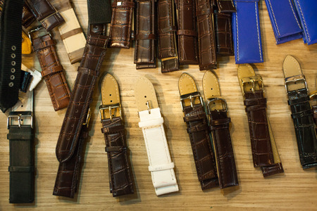 Many vintage watch straps on wood table for repair Stock Photo